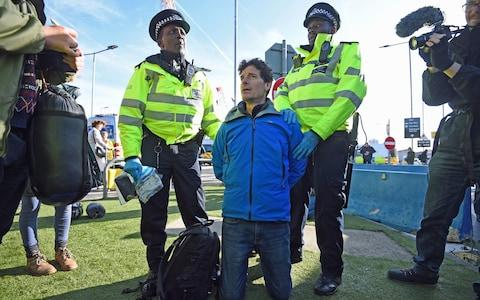 A man is arrested by police officers from the DLR station after activists staged a 'Hong Kong style' blockage of the exit from the station to City Airport - Credit: Kirsty O'Connor/PA