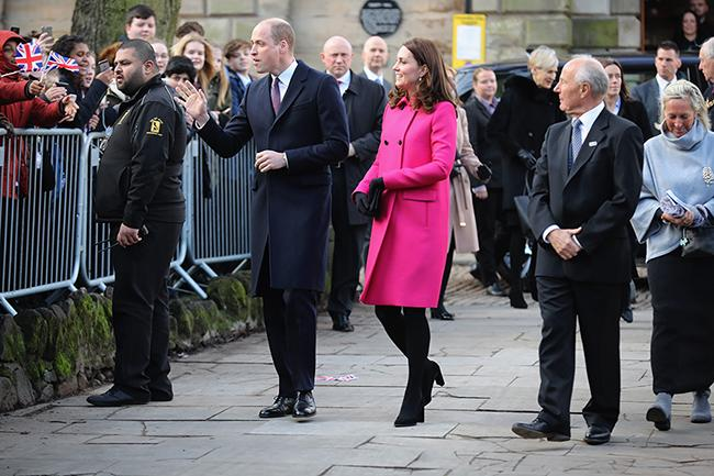 Prince William and Kate greet the crowd as they stand along the sideline of fences and security