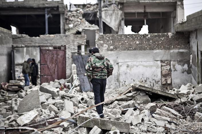 Free Syrian Army fighters walk amid the ruins of a village situated a short distance from an area where fighting between rebels and government forces continues, Saturday, Dec. 22, 2012. (AP Photo/Virginie Nguyen Hoang)