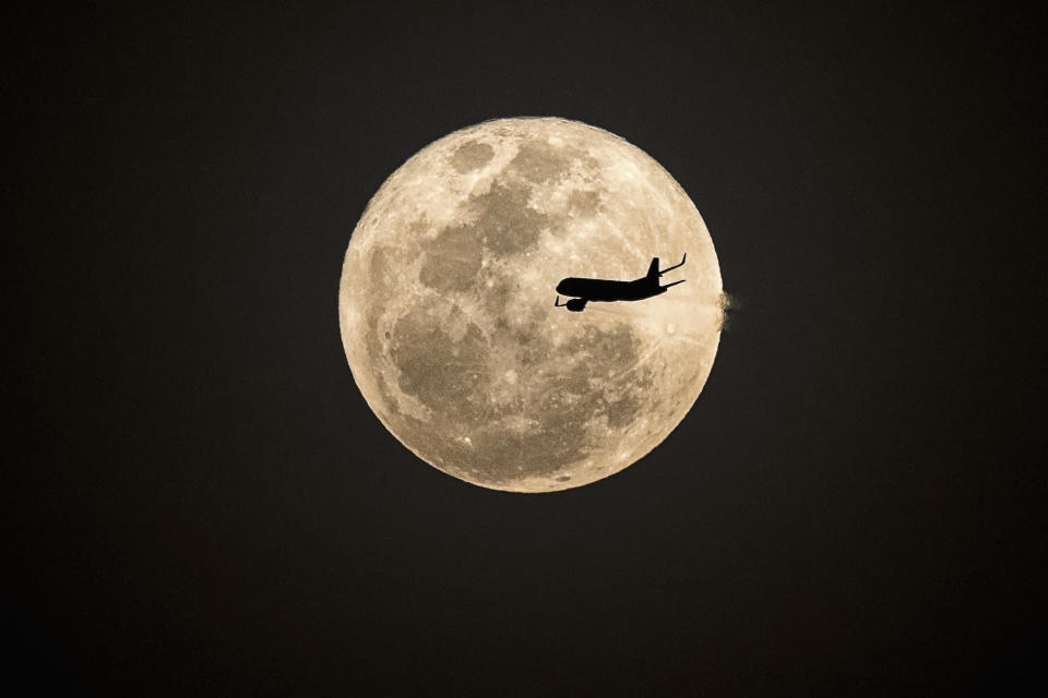 Silhouette aircraft fly in front of supermoon