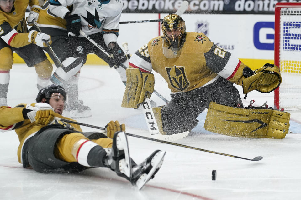 Vegas Golden Knights defenseman Nicolas Hague (14) slides across the ice after Vegas Golden Knights goaltender Marc-Andre Fleury (29) blocked a shot by the San Jose Sharks during the third period of an NHL hockey game Wednesday, March 17, 2021, in Las Vegas. (AP Photo/John Locher)