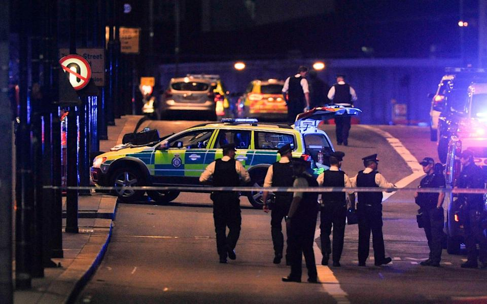 Police officers walk at the scene of an apparent terror attack on London Bridge - Credit: AFP