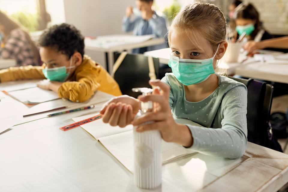 Schoolgirl with face mask using hands sanitizer while sitting at a desk in the classroom.