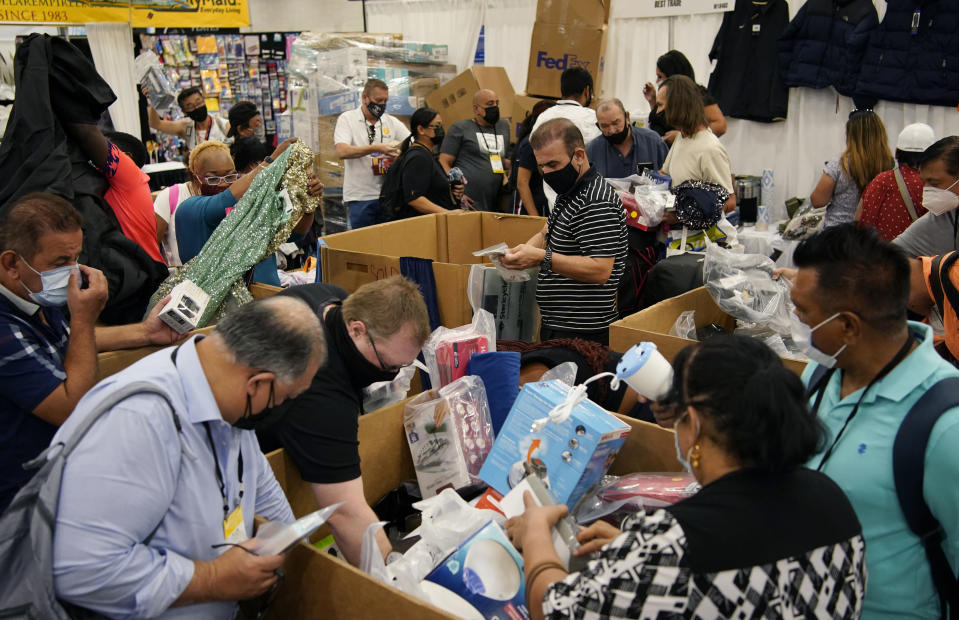 People crowd a booth looking to buy items on the final day of the convention floor at the ASD Market Week convention Wednesday, Aug. 25, 2021, in Las Vegas. In pre-COVID times, business events like conferences and trade shows routinely attracted more than 1 billion participants and $1 trillion in direct spending each year. The pandemic brought those gatherings to a sudden halt, but now in-person meetings are on the rebound from Las Vegas to Beijing. (AP Photo/John Locher)