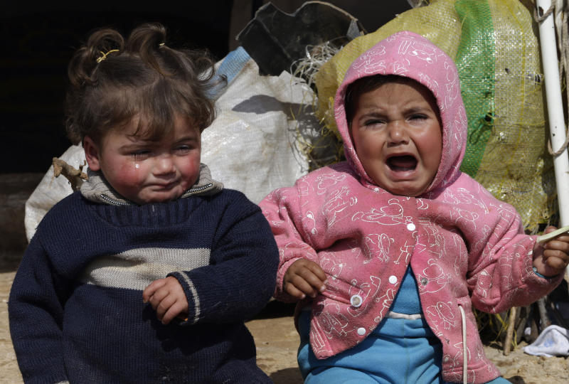 In this Tuesday, Feb. 19, 2013 photo, two Syrian refugee children sit outside their family tent, at Atmeh refugee camp, in the northern Syrian province of Idlib, Syria. This rebel-controlled camp only yards from the border with Turkey houses some 16,000 people displaced by the civil war. But the U.N. and other major aid agencies best equipped to handle such a large-scale relief agency cannot reach them because they are inside Syria. That leaves the job to smaller organizations who can only provide a fraction of the needs. (AP Photo/Hussein Malla)