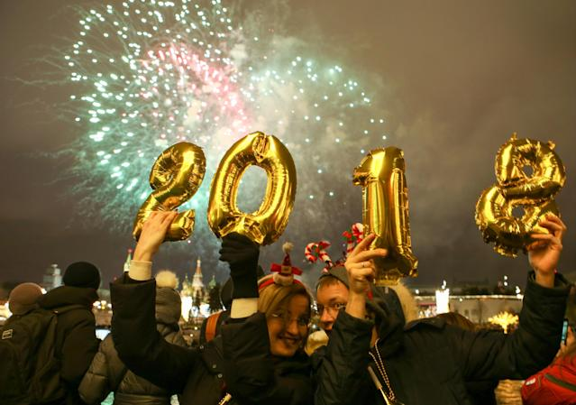 <p>People hold up balloons shaped as digits 2, 0, 1 and 8 as they watch fireworks over central Moscow during New Year celebrations. (Photo: Marina Lystseva/Getty Images) </p>