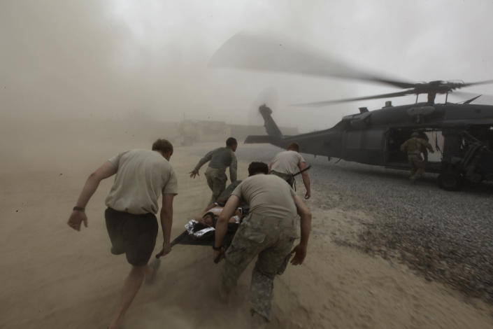 During a rescue mission by a team from a U.S. Air Force Expeditionary Rescue Squadron, army medics carry a wounded Afghan Army soldier to an evacuation helicopter, in Kandahar province, southern Afghanistan, on Aug. 2, 2010. U.S. Air Force Pararescumen and helicopter aircrews work together to evacuate wounded combatants and civilians from battlefields in southern Afghanistan. (AP Photo/Brennan Linsley, File)