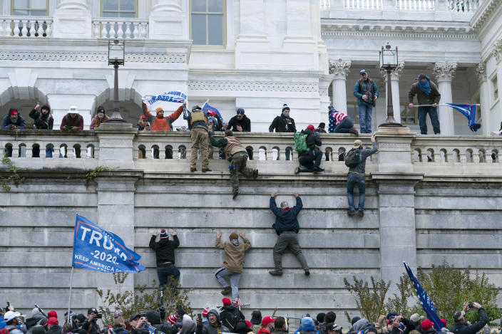 FILE - In this Wednesday, Jan. 6, 2021 file photo, supporters of President Donald Trump climb the west wall of the the U.S. Capitol in Washington. In what could be the longest of legal longshots, several of those arrested for storming the U.S. Capitol are holding out hope that President Donald Trump will use some of his last hours in office to grant all the rioters a full and complete pardon. (AP Photo/Jose Luis Magana)