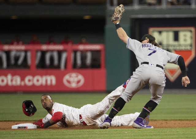 Philadelphia Phillies' Jean Segura, left, gets caught stealing with the tag by Colorado Rockies second baseman Brendan Rodgers, right, during the first inning of a baseball game Friday, May 17, 2019, in Philadelphia. (AP Photo/Chris Szagola)