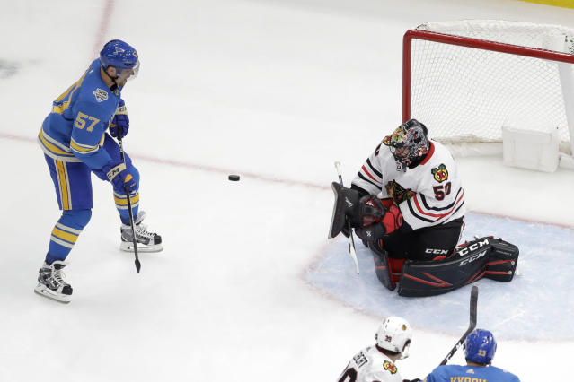 St. Louis Blues' David Perron (57) and Chicago Blackhawks goaltender Corey Crawford keep their eyes on a loose puck during the third period of an NHL hockey game Saturday, Dec. 14, 2019, in St. Louis. The Blues won 4-3. (AP Photo/Jeff Roberson)