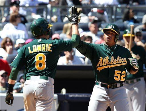 Oakland Athletics Yoenis Cespedes is congratulated by teammate Jed Lowrie after hitting a two-run home run in the fifth inning of a baseball game in New York on Sunday, May 5, 2013. (AP Photo/Peter Morgan)