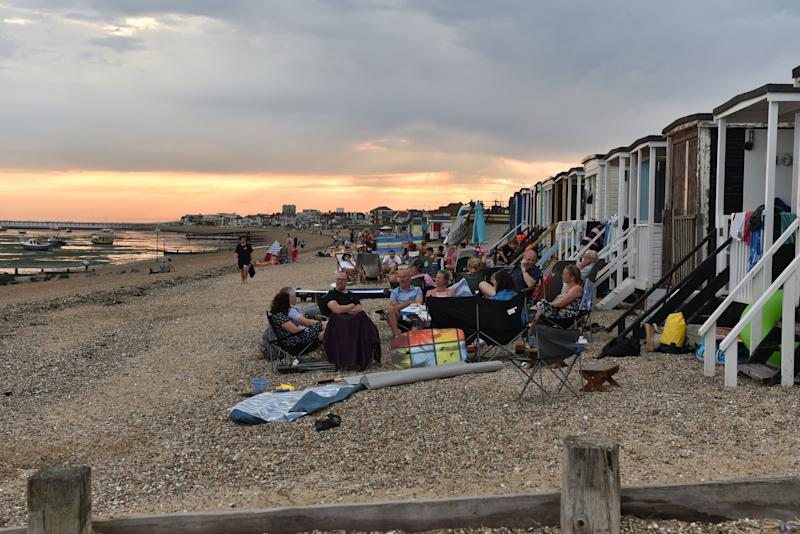 People sit on the beach into the evening as the sun set on Saturday in Southend-on-Sea. (Photo: John Keeble via Getty Images)