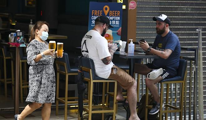People enjoy a beer at a bar at Lan Kwai Fong in Central on Monday. Photo: Nora Tam