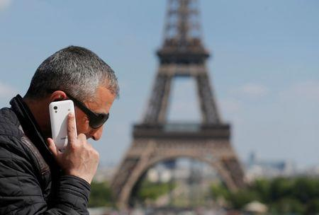 FILE PHOTO - A man makes a phone call using his mobile phone at the Trocadero Square near the Eiffel Tower in Paris
