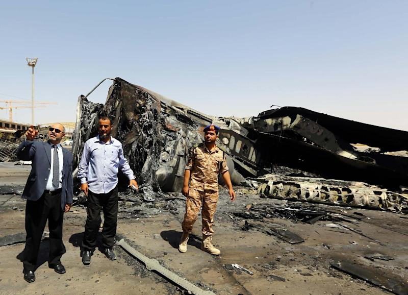 Libyan Transport Minister Mohammed Ahmed (L) inspects the destruction at Tripoli international airport in the Libyan capital on July 21, 2014 (AFP Photo/Mahmud Turkia)