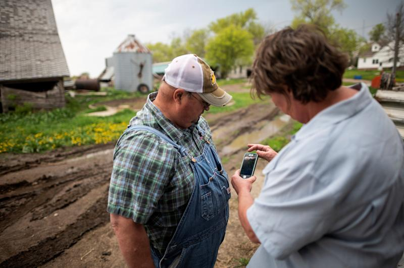 Farmer Sid Ready looks at his wifeÕs RuthÕs smart phone to check weather radar of the approaching storm, at his farm near Scribner, Nebraska on May 5, 2019. (Photo by Johannes EISELE / AFP) (Photo credit should read JOHANNES EISELE/AFP/Getty Images)