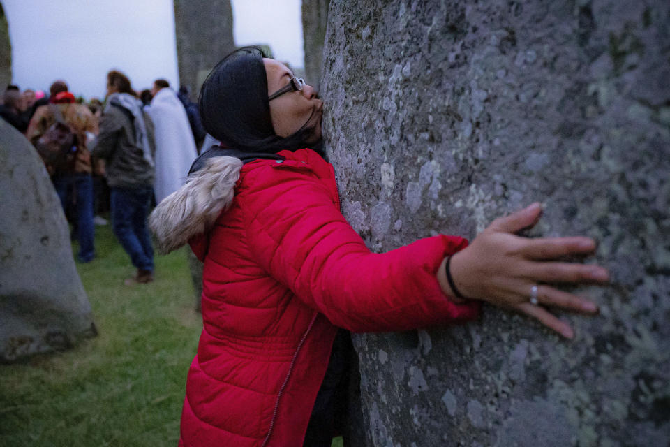 A woman kisses one of the standing stones during Summer Solstice at Stonehenge, where some people jumped over the fence to enter the stone-circle to watch the sun rise at dawn of the longest day of the year in the UK, in Amesbury, England, Monday June 21, 2021. The prehistoric monument of ancient stones have been officially closed for the celebrations due to the coronavirus lockdown, but groups of people ignored the lockdown to mark the Solstice, watched by low key security. (Ben Birchall/PA via AP)