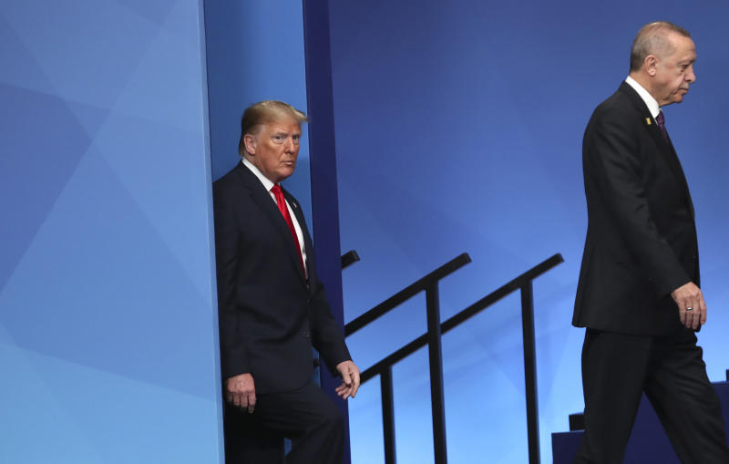 U.S. President Donald Trump, left, and Turkish President Recep Tayyip Erdogan step onto the stage to attend a ceremony event during a NATO leaders meeting at The Grove hotel and resort in Watford, Hertfordshire, England, Wednesday, Dec. 4, 2019. NATO Secretary-General Jens Stoltenberg rejected Wednesday French criticism that the military alliance is suffering from brain death, and insisted that the organization is adapting to modern challenges. (AP Photo/Francisco Seco)