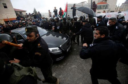 Palestinian security forces push away demonstrators from the convoy of Greek Orthodox Patriarch of Jerusalem Theophilos III, during a protest against his visit, in the West Bank city of Bethlehem January 6, 2018. REUTERS/Mussa Qawasma