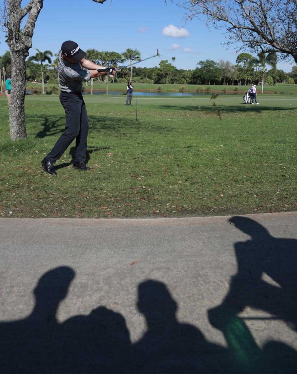 The shadows of golf fans are cast on the cart path as Justin Thomas hits from out of bounds on the ninth hole during the third round of the Honda Classic golf tournament, Saturday, March 2, 2019, in Palm Beach Gardens, Fla. (AP Photo/Wilfredo Lee)