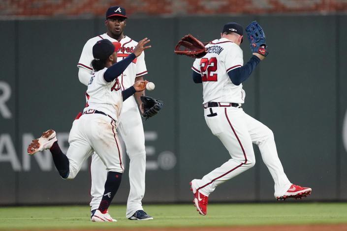 Atlanta Braves second baseman Ozzie Albies, right fielder Jorge Soler and center fielder Joc Pederson, from left, can't catch a fly ball hit hit San Francisco Giants' Brandon Crawford during the sixth inning of a baseball game Saturday, Aug. 28, 2021, in Atlanta. (AP Photo/John Bazemore)