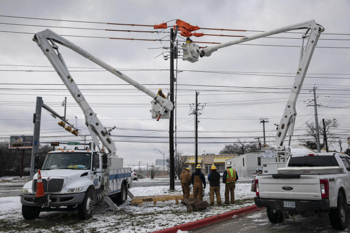 Utility workers repair a burnt-out switch in Austin, Texas, Thursday, Feb. 18, 2021.  (Tamir Kalifa/The New York Times)