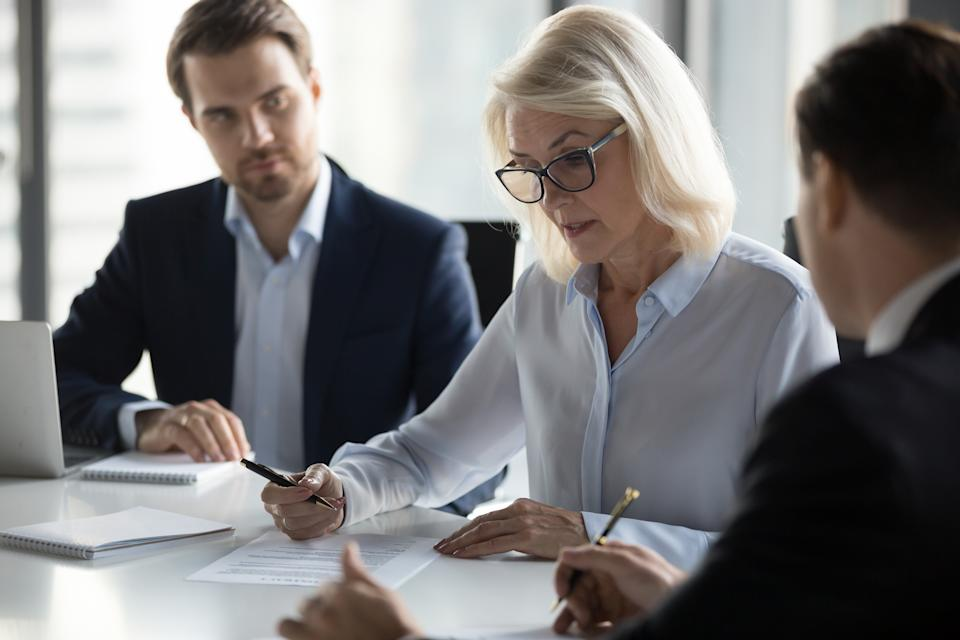 Businessmen sitting at desk headed by middle aged serious concentrated female in eyeglasses checking agreement document before signing it. Financial director ready affirm official paper with signature
