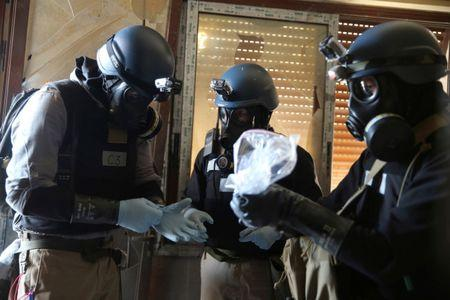 FILE PHOTO: UN chemical weapons expert holds a plastic bag containing samples from one of the sites of an alleged chemical weapons attack in Ain Tarma