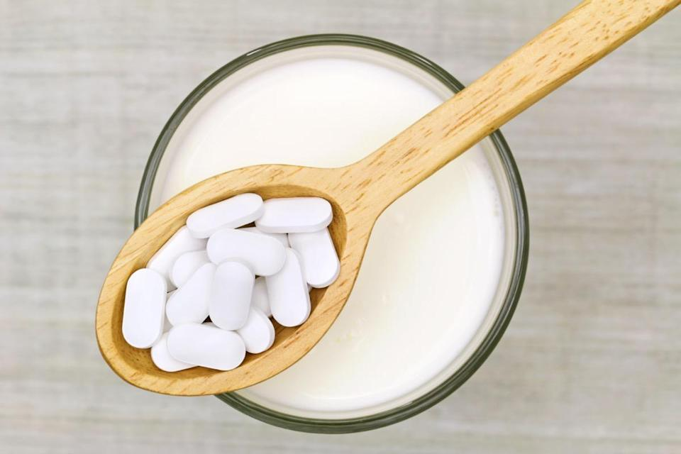 Wooden spoon of Calcium carbonate tablets above glass of milk