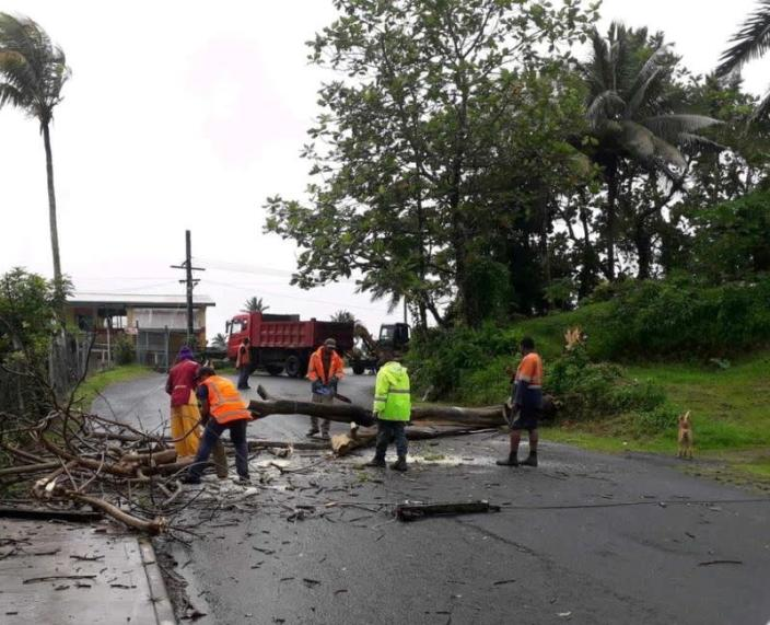 People remove debris due to Cyclone Yasa at Velau Drive in Fiji