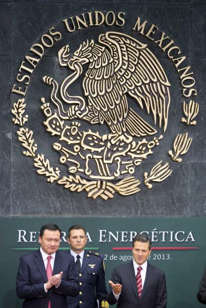 Mexico's President Enrique Pena Nieto, right, greets the audience as his Interior Secretary Miguel Angel Osorio Chong, left, applauds upon his arrival to the ceremony to announce his proposal that would allow private firms in the oil industry in Mexico City, Monday, Aug.12, 2013. Pena Nieto is making his most daring gamble yet, with a proposal to lift a decades-old ban on private companies in the state-run oil industry, a cornerstone of Mexico's national pride. (AP Photo/Eduardo Verdugo)