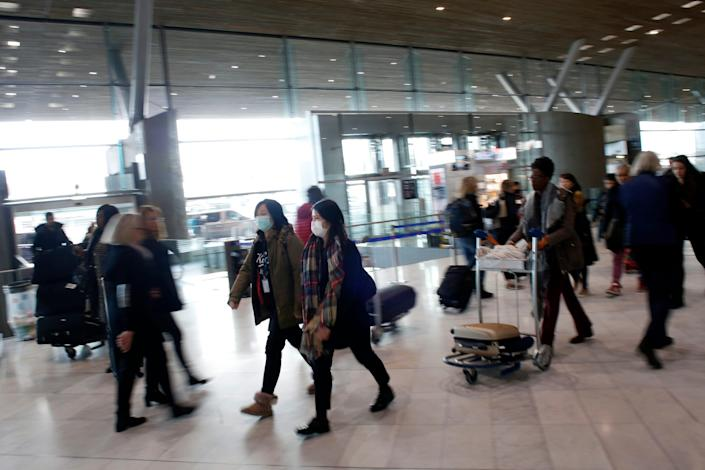 Women wear face masks at the Charles de Gaulle airport, north of Paris, Thursday, March 12, 2020. The European Union on Thursday will evaluate President Donald Trump's decision to restrict travel from Europe to the United States amid deep concern over the economic impact of the move with markets already heavily hit by coronavirus.
