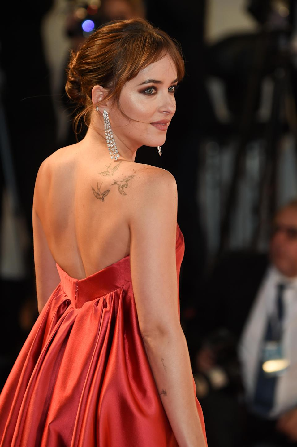 <p>Actress Dakota Johnson has a number of tattoos but it's widely believed the birds on her right shoulder hold a special meaning. It's reported that the ink is in tribute to her grandmother Tippi Hedren who starred in Alfred Hitchcock's 1963 flick, 'The Birds'. <em>[Photo: Getty]</em> </p>