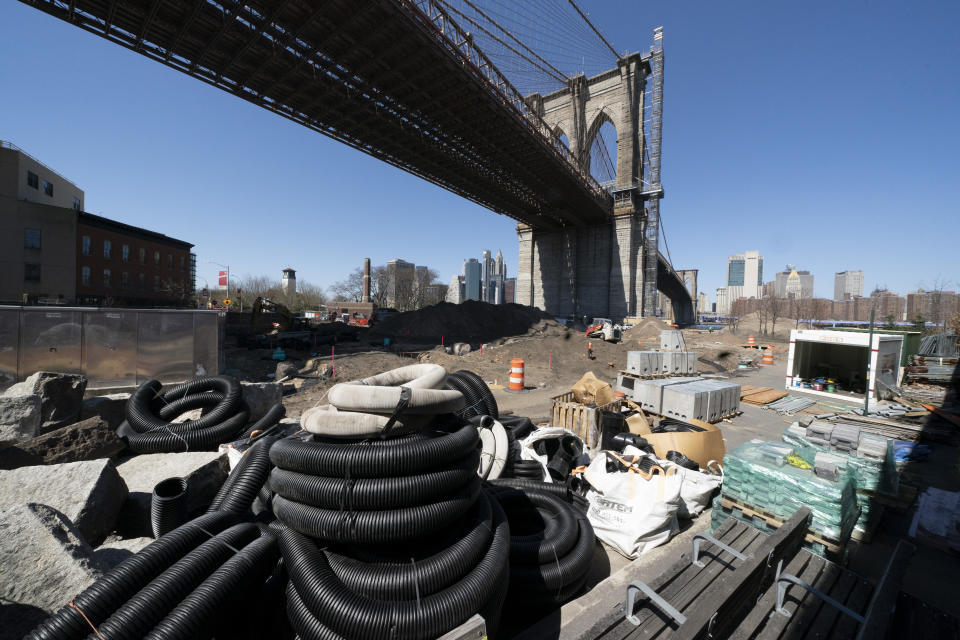 Work continues on the Emily Roebling Plaza underneath the Brooklyn Bridge, Tuesday, April 6, 2021 in New York. With an appeal to think big, President Joe Biden is promoting his $2.3 trillion infrastructure plan directly to Americans. Republicans oppose Biden's American Jobs Plan as big taxes, big spending and big government. (AP Photo/Mark Lennihan)