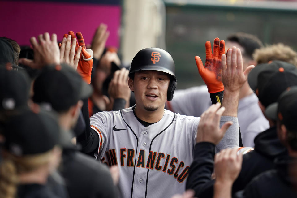 San Francisco Giants' Wilmer Flores celebrates his two-run home run with teammates in the dugout during the first inning of a baseball game against the Los Angeles Angels Tuesday, June 22, 2021, in Anaheim, Calif. (AP Photo/Marcio Jose Sanchez)