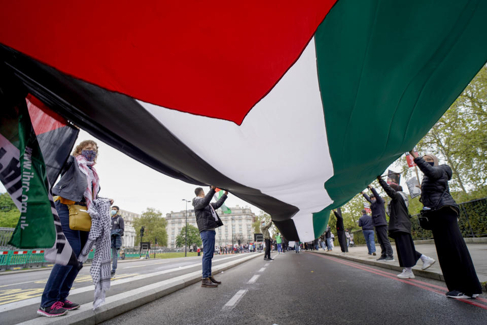 People hold a Palestinian flag as they march in solidarity with the Palestinian people amid the ongoing conflict with Israel, during a demonstration in London, Saturday, May 15, 2021. (AP Photo/Alberto Pezzali)