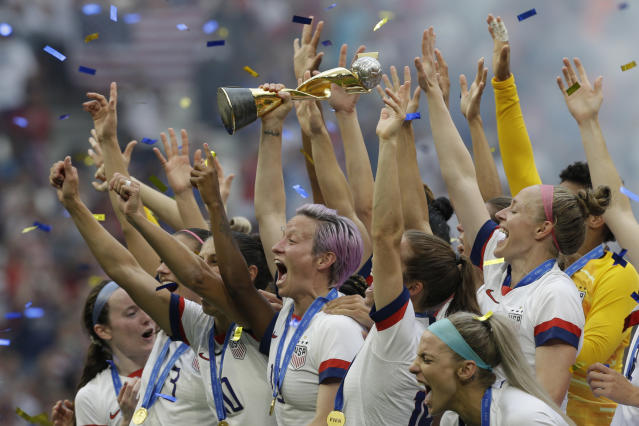 FILE - In this July 7, 2019, file photo, U.S. player Megan Rapinoe holds the trophy after winning the Women's World Cup final soccer match against The Netherlands at the Stade de Lyon in Decines, outside Lyon, France. Rapinoe is enjoying the whirlwind of a two-time World Cup winner. She picked up the FIFA Player of the Year award in Milan rocking a deeper shade of lavender hair, sent off retiring U.S. coach Jill Ellis with an undefeated victory tour and kept up the fight for pay equity against the U.S. Soccer Federation. (AP Photo/Claude Paris, File)