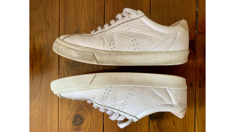 Two sneakers, one dirty and one cleaned with the Scrub daddy eraser