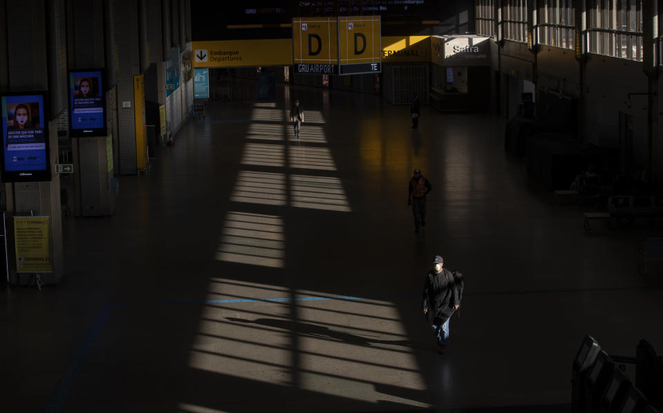A few people walk through an empty corridor inside the Sao Paulo International Airport in Guarulhos, Brazil, Wednesday, May 27, 2020. According to the airport administration, Brazil's busiest airport has had an average reduction of 85% in flights, due to the COVID-19 pandemic. (AP Photo/Andre Penner)