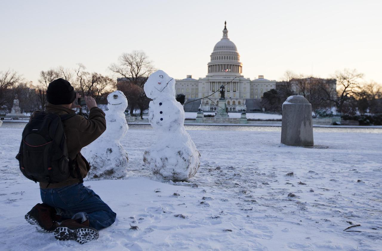 A man takes photos of snowmen with the Capitol in the background, Friday, Jan. 3, 2014, in Washington. After a storm blew through the Washington region overnight, roads are being cleared and many schools systems are closed. The federal government and the District of Columbia government will be open Friday, but workers have the option to take leave or telework. (AP Photo/ Evan Vucci)