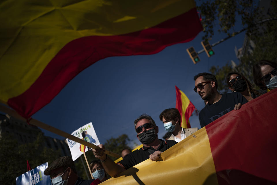 Demonstrators march during a celebration for Spain's National Day in Barcelona, Spain, Tuesday, Oct. 12, 2021. Spain commemorates Christopher Columbus' arrival in the New World and also Spain's armed forces day. (AP Photo/Joan Mateu Parra)