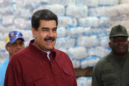 Venezuela's President Nicolas Maduro smiles during his visit to a packing center of the CLAP program, in Caracas