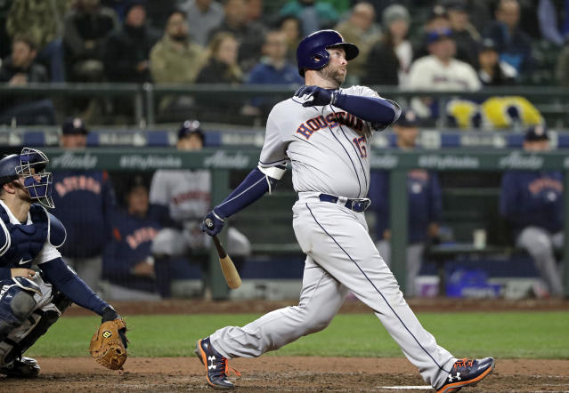 FILE - In this April 17, 2018, file photo, Houston Astros' Brian McCann, right, and Seattle Mariners catcher Mike Marjama watch the path of McCann's two-run home run in the sixth inning of a baseball game in Seattle. A person familiar with the negotiations tells The Associated Press that McCann has agreed to return to the Atlanta Braves for a $2 million, one-year contract. The person spoke on condition of anonymity Monday, Nov. 26, 2018, because the agreement had not yet been announced. (AP Photo/Elaine Thompson, File)