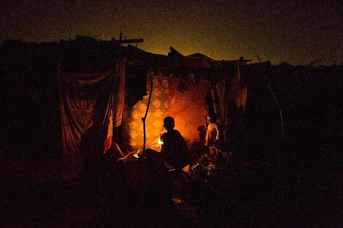 A woman cooks in a tent in the refugee camp at M'Poko airport, in Bangui, Central African Republic, on February 22, 2014 (AFP Photo/Fred Dufour)