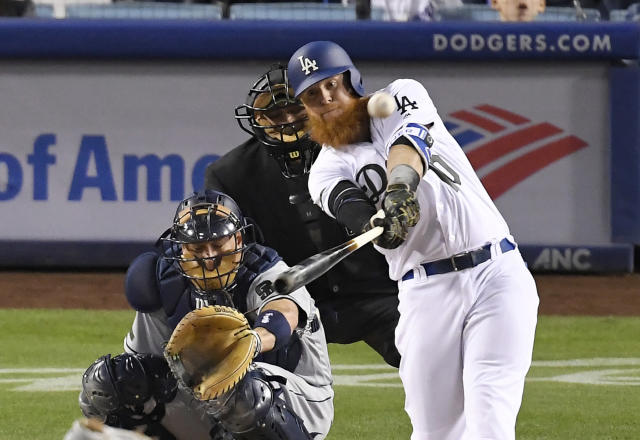 Los Angeles Dodgers' Justin Turner hits a solo home run as San Diego Padres catcher A.J. Ellis, left, and home plate umpire Brian Knight watch during the fourth inning of a baseball game Saturday, May 26, 2018, in Los Angeles. (AP Photo/Mark J. Terrill)