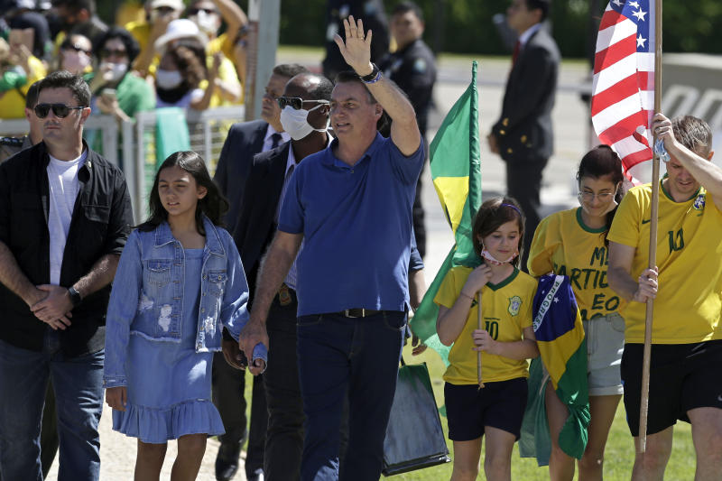Brazil's President Jair Bolsonaro holds his daughter's hand as he waves to supporters during a protest against his former Minister of Justice Sergio Moro and the Supreme Court, in front of the Planalto presidential palace, in Brasilia, Brazil, Sunday, May 3, 2020. (AP Photo/Eraldo Peres)