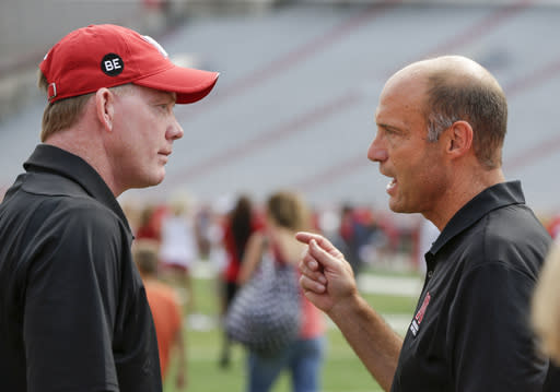 Nebraska football head coach Mike Riley (R) chats with Shawn Eichorst during fan day in Lincoln. Nebraska fired Eichorst on Thursday. (AP)
