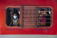 A boy wearing a face mask looks through the window of a train at a railway station in Gauhati, India, Monday, April 19, 2021. India now has reported more than 15 million coronavirus infections, a total second only to the United States. (AP Photo/Anupam Nath)