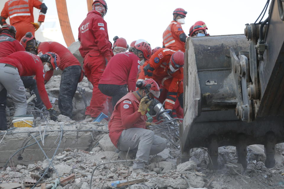 Members of rescue services search in the debris of a collapsed building for survivors in Izmir, Turkey, Sunday, Nov. 1, 2020. Rescue teams continue ploughing through concrete blocs and debris of collapsed buildings in Turkey's third largest city in search of survivors of a powerful earthquake that struck Turkey's Aegean coast and north of the Greek island of Samos, Friday Oct. 30, killing dozens Hundreds of others were injured.(AP Photo/Darko Bandic)