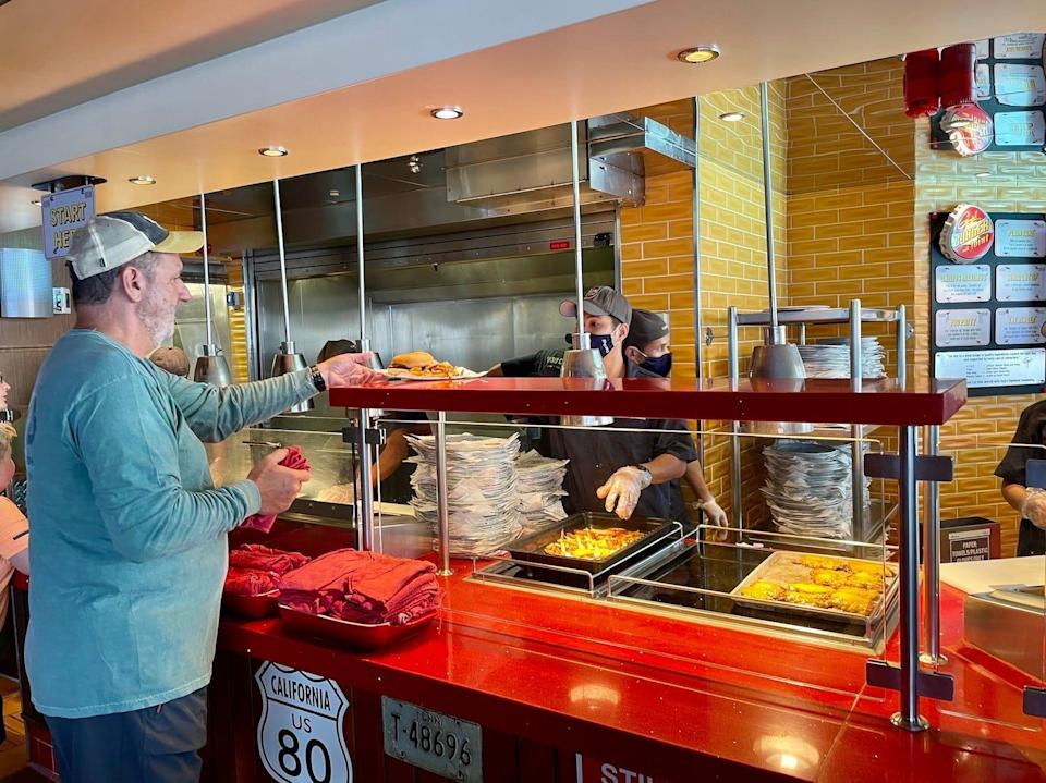 A passenger grabs his burger from Guy's Burger Joint on the Carnival Vista.